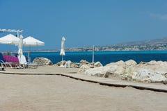 Часть пляжа с зонтиками и кроватями планки, на фоне неба и моря стоковые изображения