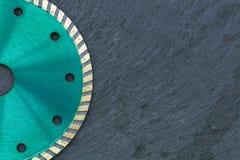 Часть режущего диска диаманта изумрудного цвета на фоне серого гранита стоковые изображения