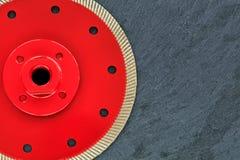 Часть режущего диска диаманта красна с продетой нитку гайкой на предпосылке серого гранита стоковое фото