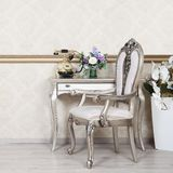 Часть ретро интерьера с стулом и столом на котором расположены телефон и ваза цветков стоковая фотография