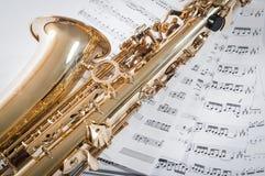 Часть саксофона лежа на примечаниях Стоковые Изображения