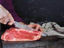 Часть свежей говядины на мраморной темноте деревянная доска Мужская рука с ножом Резать мясо в стейки Стоковые Изображения
