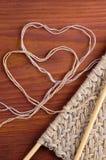 Часть связанной ткани с деревянными иглами и сердцами потока на деревянном столе Стоковые Изображения RF