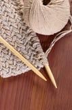 Часть связанной ткани с потоками и деревянными иглами на деревянном столе Стоковая Фотография RF