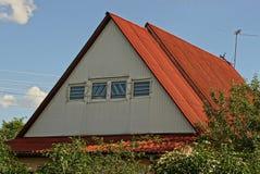 Часть сельского дома от чердака с окном под красным шифером против неба стоковая фотография rf