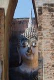 Часть скульптур гигантских Будды, смотря от руин старого буддийского виска приятеля Wat Si Sukhothai, Таиланд Стоковые Фотографии RF