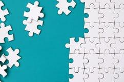 Часть сложенной белой мозаики и куча uncombed элементов головоломки на фоне голубой поверхности текстура стоковые изображения rf