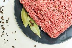 Часть сочного свежего семенить мяса на черной плите на деревянном столе с перцем и лист залива Взгляд сверху стоковое изображение rf