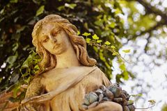 Часть старого ангела скульптуры в золотом зареве в старом кладбище Стоковая Фотография RF