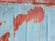 Часть старого ржавого изогнутого железного листа покрашенного в сини, с частями ржавчины оранжевого оттенка в местах куда краска  Стоковое Изображение