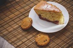 Часть торта губки на круглой белой плите с bis шоколада стоковое изображение