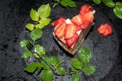 Часть торта губки со сливк сметаны, свежими клубниками на верхней части, положении на черном подносе стоковая фотография
