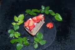 Часть торта губки со сливк сметаны, свежими клубниками на верхней части, положении на черном подносе, стоковая фотография
