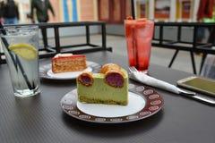 часть торта фисташки с profiteroles на таблице кафа улицы Стоковые Изображения