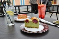 часть торта фисташки с profiteroles на таблице кафа улицы Стоковое Изображение RF