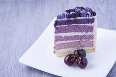 Часть фиолетового торта на таблице стоковое фото rf