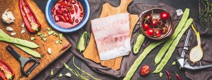 Часть филе рыб на деревенской разделочной доске при сезонные овощи варя ингридиенты и томатный соус, темное введенное в моду back Стоковое Фото