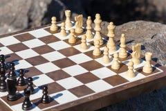 Часть шахматной доски с шахматными фигурами на камне с утесом на Стоковые Фото