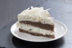 Часть шоколадного торта с сливк кокоса стоковые изображения
