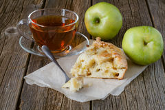 Часть яблочного пирога charlotte, зеленых сочных яблок и чашки te Стоковое Изображение RF