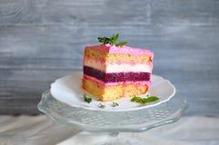 Часть striped торта в отрезке, состоя из песка, белизна, пинк, темнота - красные слои, при части мяты лежа на белой плите дальше Стоковое Изображение