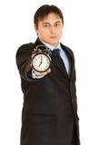 часы бизнесмена сигнала тревоги держа серьезных детенышей Стоковые Изображения