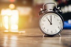 часы времени часов ` 11 o ретро на деревянной таблице с солнечным светом Стоковое Изображение