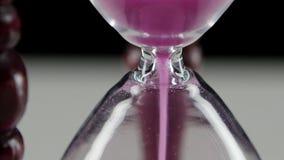 Часы в деревянной стойке Розовый песок конец вверх видеоматериал