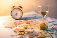 Часы и валюта на таблице, концепция вклада времени Стоковые Фотографии RF