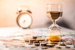 Часы и валюта на таблице, концепция вклада времени Стоковое Фото