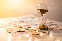 Часы и валюта на таблице, концепция вклада времени Стоковые Фото