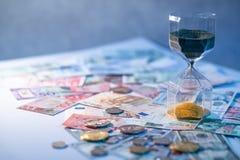 Часы и валюта на таблице, концепция вклада времени Стоковая Фотография RF