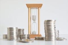Часы и некоторые кучи монетки против белой предпосылки стоковые фотографии rf