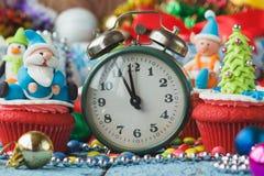 Часы и пирожные рождества с покрашенными украшениями Стоковая Фотография