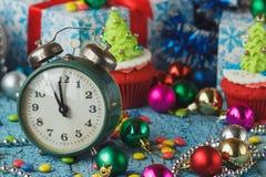 Часы и пирожные рождества с покрашенными украшениями Стоковые Изображения
