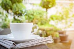 часы кофейной чашки и бумага новостей на старом backg природы деревянного стола Стоковое Фото