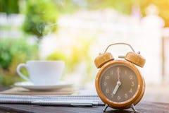часы кофейной чашки и бумага новостей на старом backg природы деревянного стола Стоковое фото RF