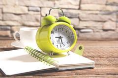 Часы на блокноте и кофе на столе стоковые изображения