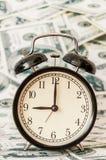 Часы на предпосылке картины долларовой банкноты месяца наличных денег Стоковые Изображения RF