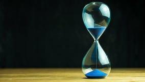 Часы песка промежутка времени на деревянном столе и черной предпосылке сток-видео