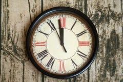 Часы старого стиля классические с римскими номерами показывая почти 12 часов Приурочьте почти веденный или пришл, на деревянное b стоковое изображение