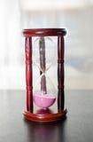 Часы, стекло песка на таблице Стоковые Изображения