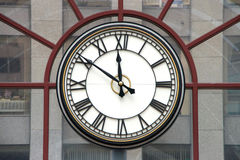 Часы с римскими цифрами на стеклянной стене Стоковое Фото