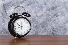 часы часов ` 10 o винтажные на деревянной предпосылке таблицы и стены Стоковые Изображения