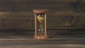 Часы Sandglass на деревянном столе сток-видео