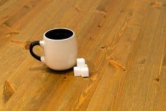 Чашка Брайна и кубы сахара на деревянном столе Стоковая Фотография RF