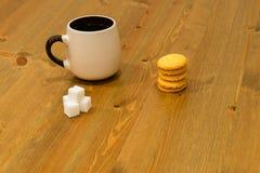 Чашка Брайна, кубы сахара и печенья на деревянном столе Стоковые Изображения RF