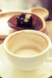 Чашка выпивая кофе на деревянном столе с плитой нерезкости пирожного на предпосылке Стоковая Фотография RF