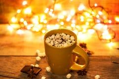 Чашка горячего какао с зефирами и шоколадом на деревянной предпосылке с красивыми светами рождества стоковые изображения