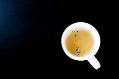 Чашка горячего кофе в белой кружке на черной предпосылке Стоковые Изображения RF